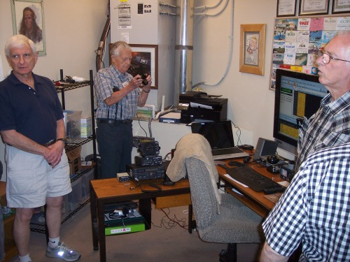 The Aspens Amateur Radio Club, K5ASP, shack is in a maintenance room on the third floor of the lodge. One of two operating positions is visible. This position includes a modern solid-state transceiver, a software defined radio (SDR), and a computer with an extra large display. A printer next to the air-conditioning unit provides convenient printouts from the computer. QSL cards received from contacted amateur radio stations are displayed on the wall.