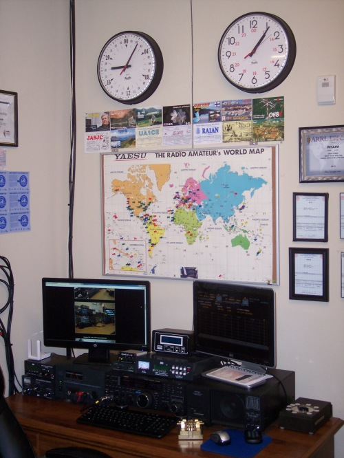One of two operating positions in the K5ASP amateur radio shack. This includes two-way amateur radio equipment and computer. Wall clocks display Coordinated Universal Time (UTC) and local time. Flags on the wall map of the world indicate locations of stations contacted by K5ASP.