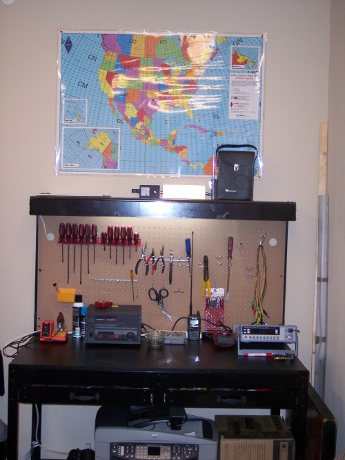 The K5ASP radio shack includes a well equipped work bench for construction projects and repairs. A printer, scanner, fax, and copier unit sits on the bottom shelf of the workbench. A map on the wall above the workbench identifies Canada and United States of America grid squares defined by the Maidenhead Locator System.