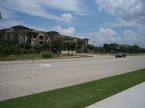 A view of The Aspens at Twin Creeks looking to the northeast across Bray Central Drive in Allen, Texas. Lodge and cottage residences are provided along with a variety of luxury amenities.